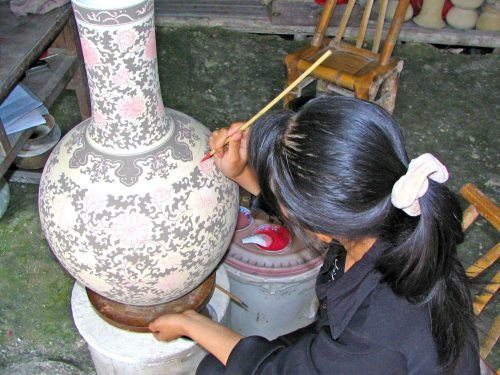 Woman Hand-Painting a Ceramic Jar in Jiujiang
