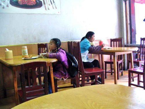 A Little Tibetan Girl Watching Television Whilst Having Breakfast